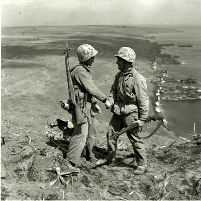 """Cpl. Harold """"Pie"""" Keller, right, shakes hands with Sgt. Howard Snyder (KIA), left, as they stand on the rim of Mt. Suribachi on Iwo Jima between the first and second flag raisings on February 23rd, 1945 (Official Army photo, courtesy of Pfc. George Burns, George Burns Collection, U.S. Army Heritage and Education Center)."""